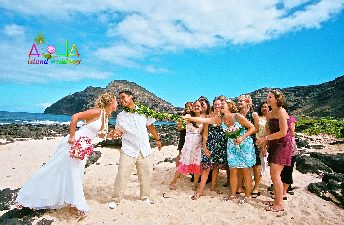 Hawaii beach wedding Girls wanna have some fun holding the groom back fom the kiss for the bride