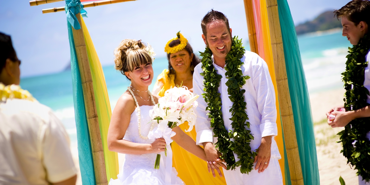 beach wedding cermeony with tiki men and hawaiian flower theme