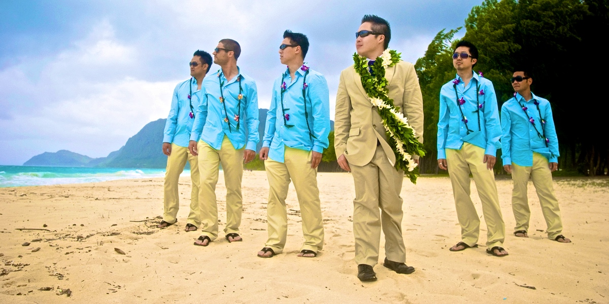 groom wearing maile lei with white orchids with groomsmen