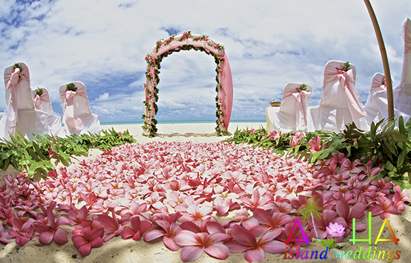Hawaii beach wedding photo with pink themed tropical flowers on the sand