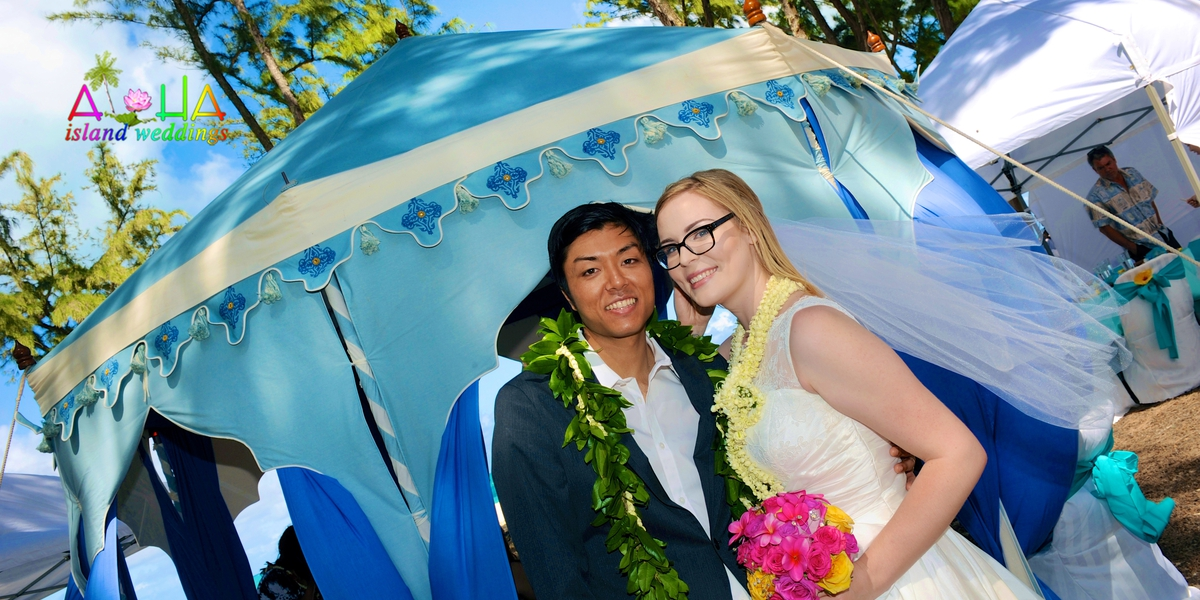 rachelle and her groom by the tent at beach reception