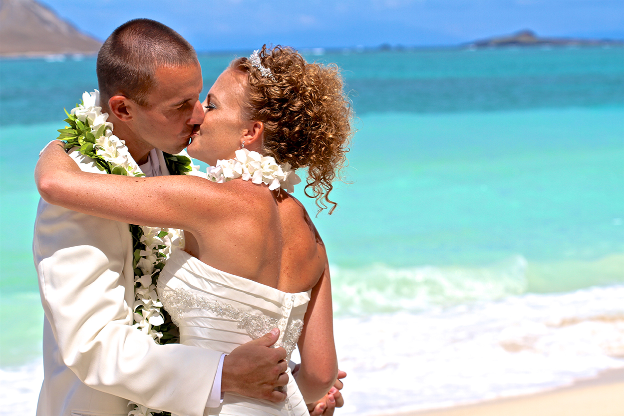 kissing her newly wed husband after her ceremony wedding on the sands of Waimanalo