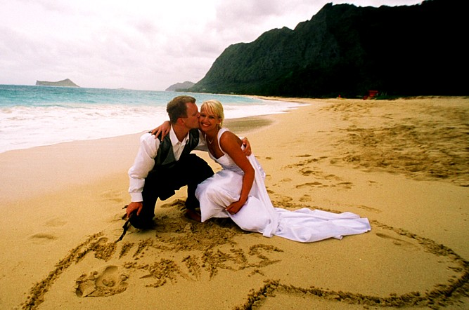 writing their names on the sand at thier beach wedding in Hawaii