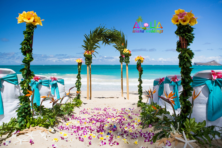 Hawaiian palm arch with bamboo brids of paradise green laupaka and yellow and pink hibiscus for the tropcial Hawaiian feel
