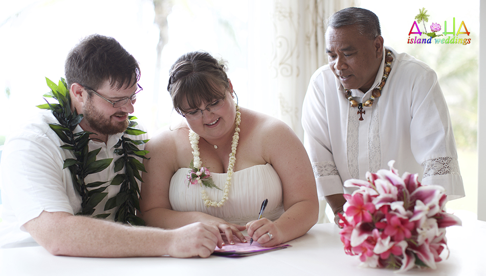 Rev Joffry looks on as the couple is sign their legal wedding license from the state of Hawaii