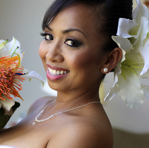 Sally holding her Hawaiian lilly protea bouquet with large white flower in the hair