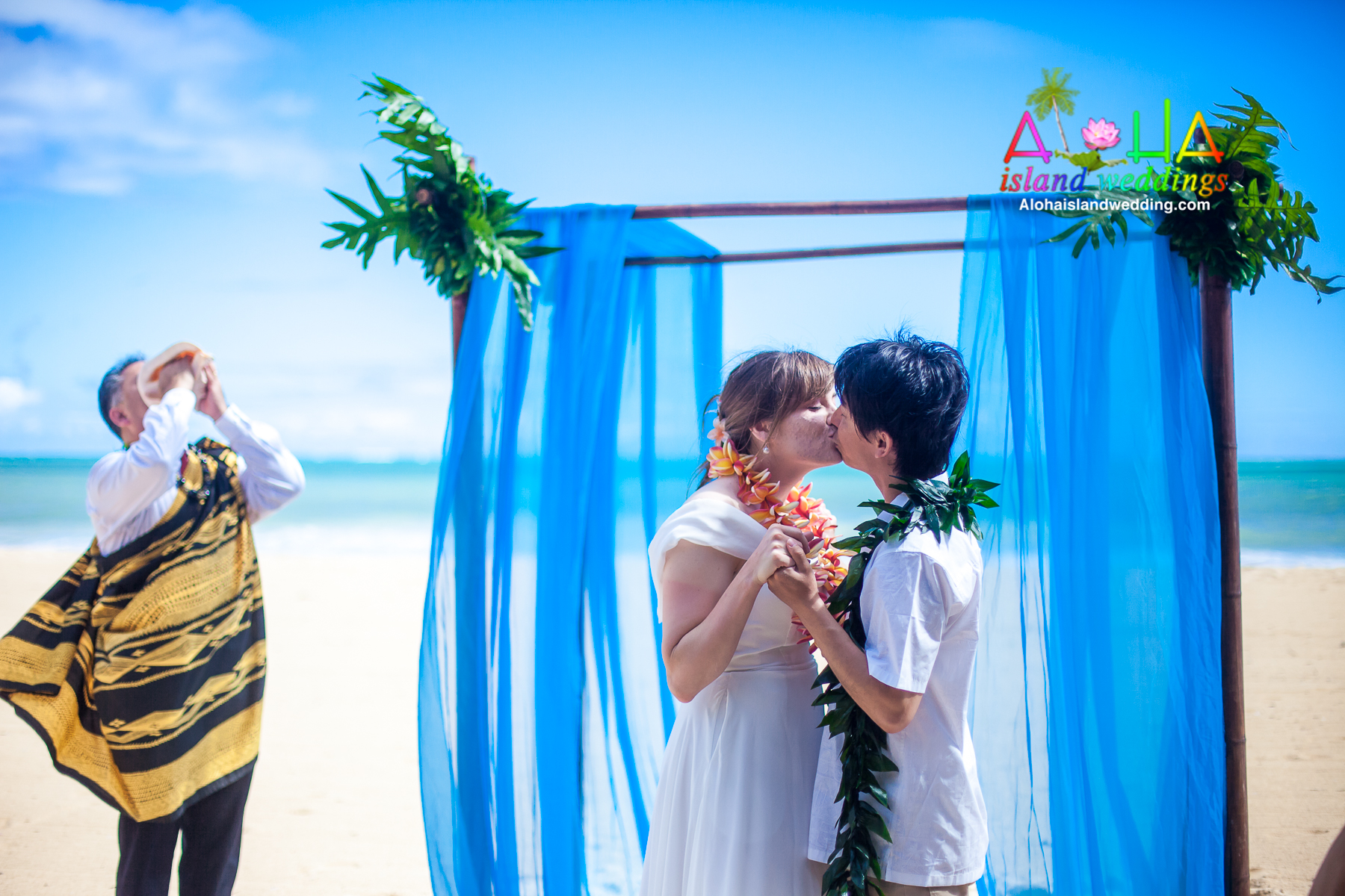 kissing under thier Hawaii wedding archway of sky blue theme while the minister blows the conch shell
