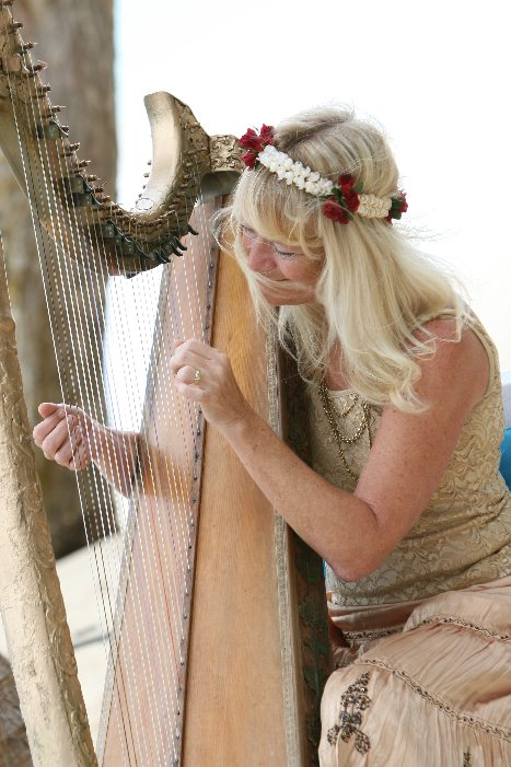 Kim Marie playing the harp at a wedding in Hawaii