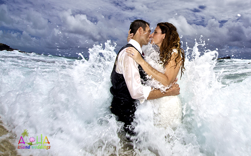 a kiss in the pacific ocean as the wave of love crashes over the newly weds