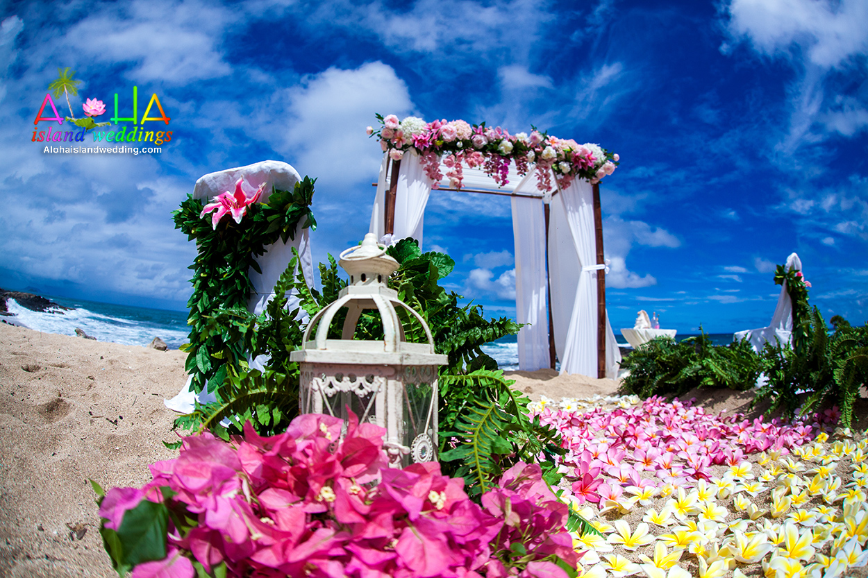 yellow and pink plumerias on the sand with candel holders and kupu kupu fern moving down the fair aisle way with a pink and dark pink themed archway
