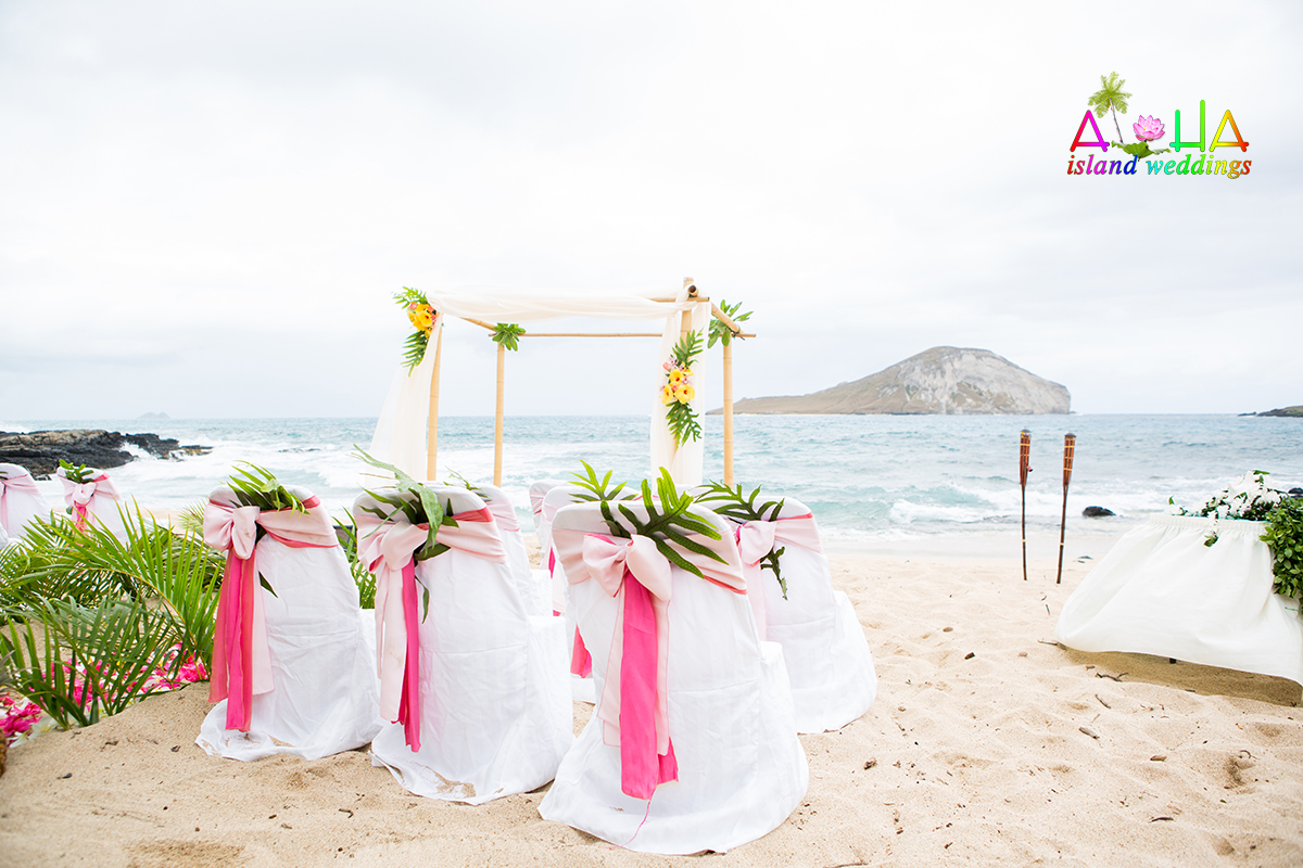 Tiki torches on the sand next to a beach wedding arch in Hawaii with light and dark pink sashes with palms for the aisle way