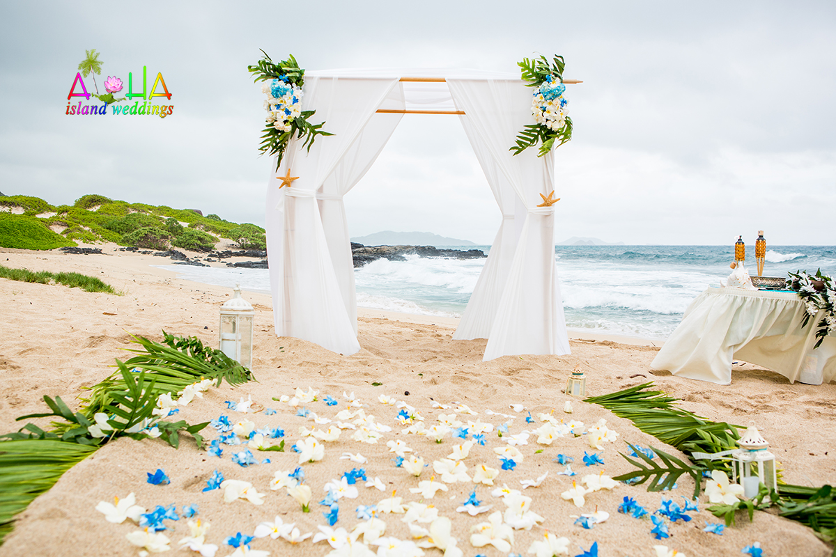 A Pure white beach wedding  bamboo arch with beach laterns and palm leaves for the side