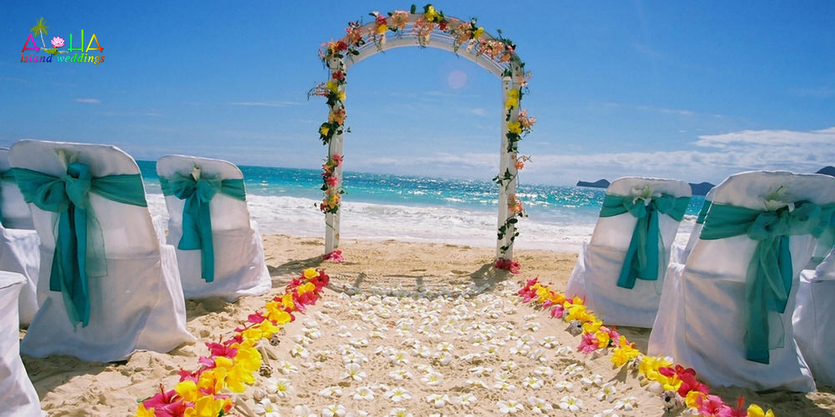 turquiose sash with sparkling waters of Bellows beach with white flowers of plumerias on the sand