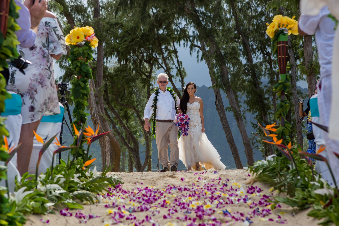 The bride is escorted down the pathway with her father to meet her husband to be