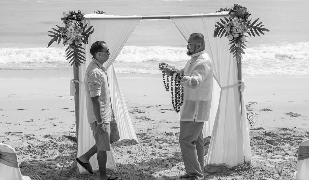 giving his best man a kukui tea leaf lei black and white beach wedding in Hawaii