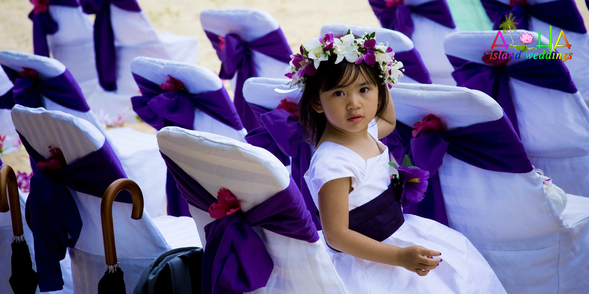 Purple sash color around the white chair cover with a flower girl