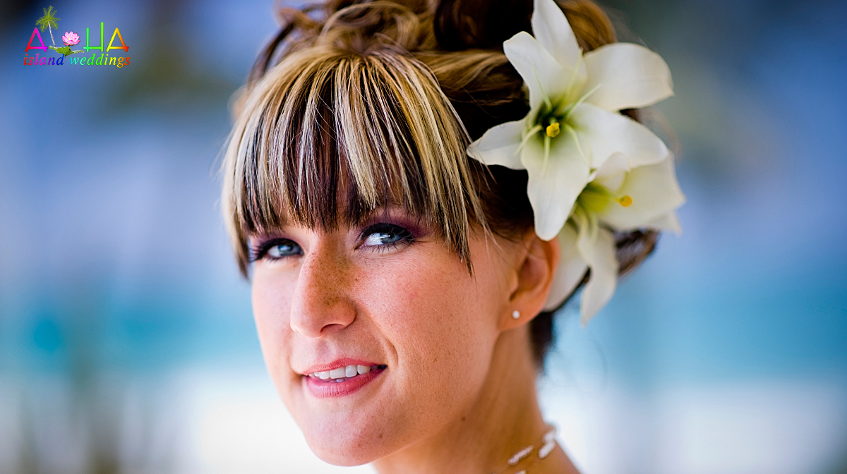 The bride bechy smiling wuith a white large flower lilly