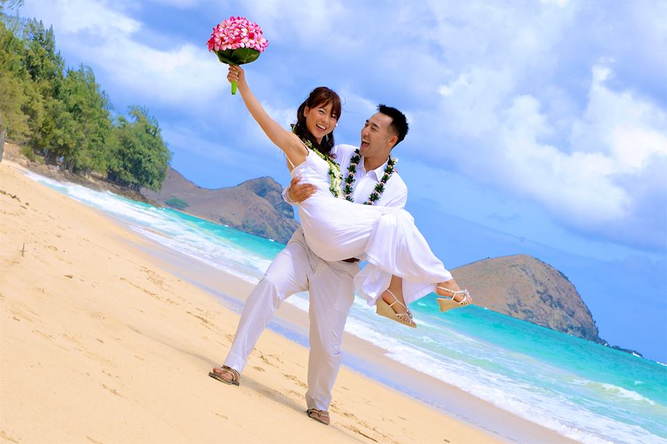 the groom holding his new wife after their Hawaii wedding with flower leis and a smile