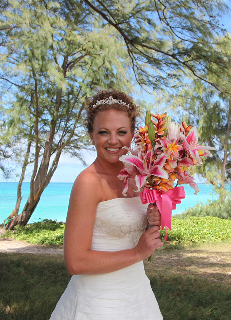 holding her bouquet of bright flowers before her beach wedding