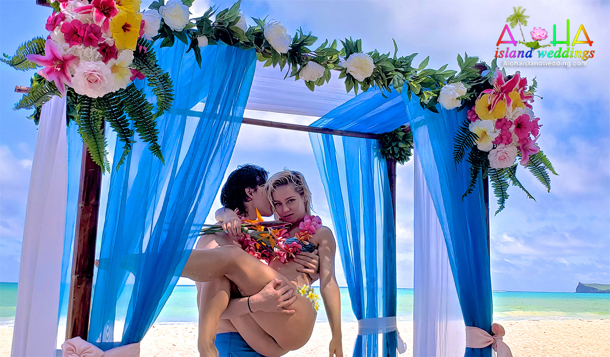 beach wear bride in her bikini with her groom taking photos on Oahu in Hawaii under the blue archway