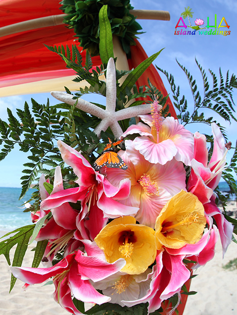 starfish on the flower arrangement of the beach arch with Hawaiian fern and pink flowers