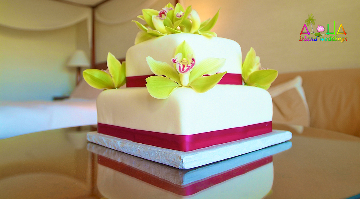 green orchids on a dark pink magenta ribboned cake