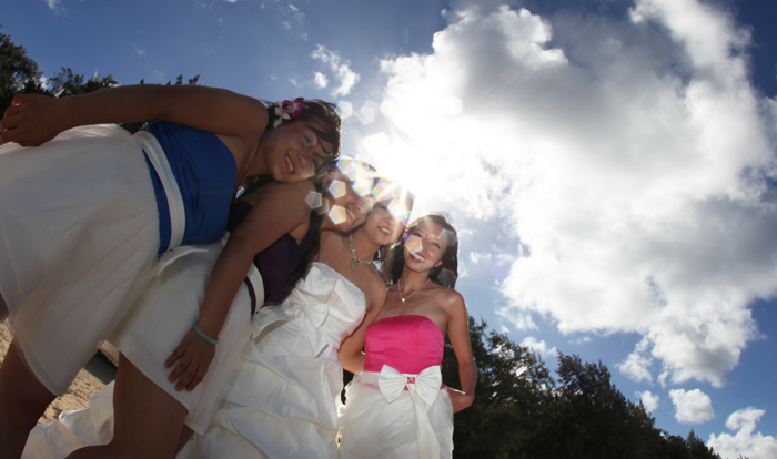 bridesmaids with a smile while the sunshines through the clouds in hawaii on the sandy shore