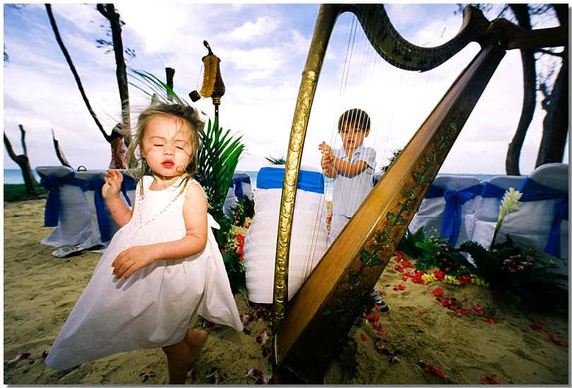 Child in wonder while playing the harp at a wedding on the beach