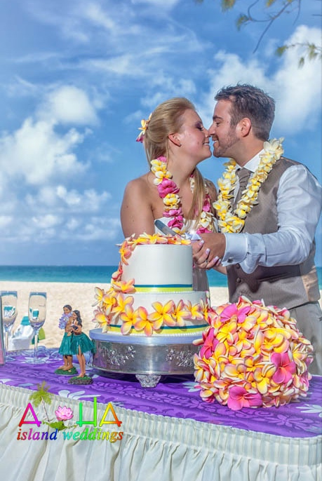 Chris cuts the cake with his bride as they give eachother Hawaiian kisses
