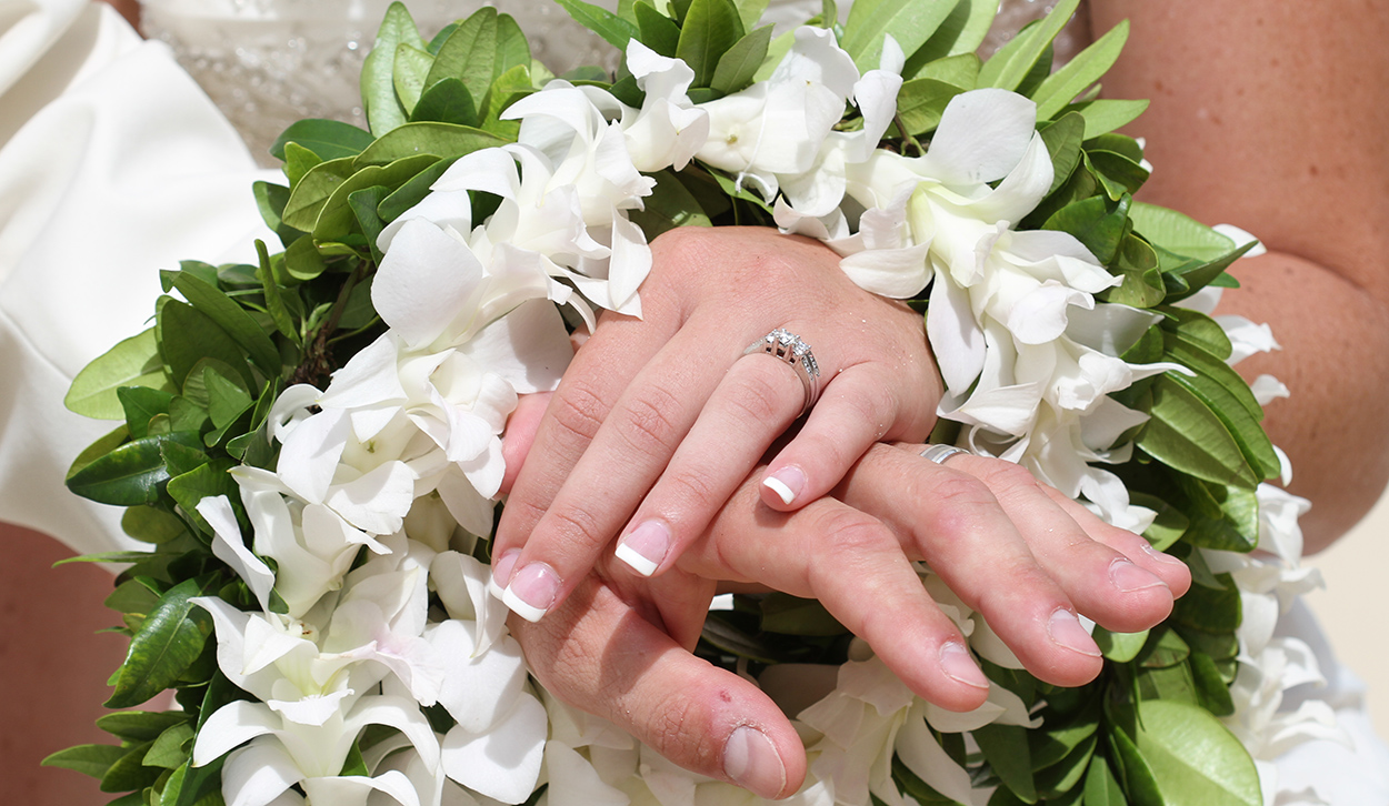 The wedding rings with flower leis of Maile and white orchids