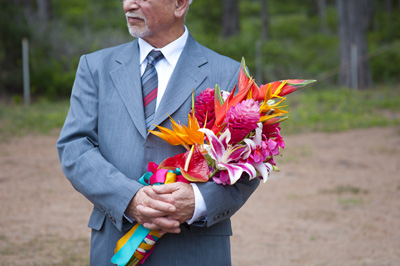 father holds the brides bouquet