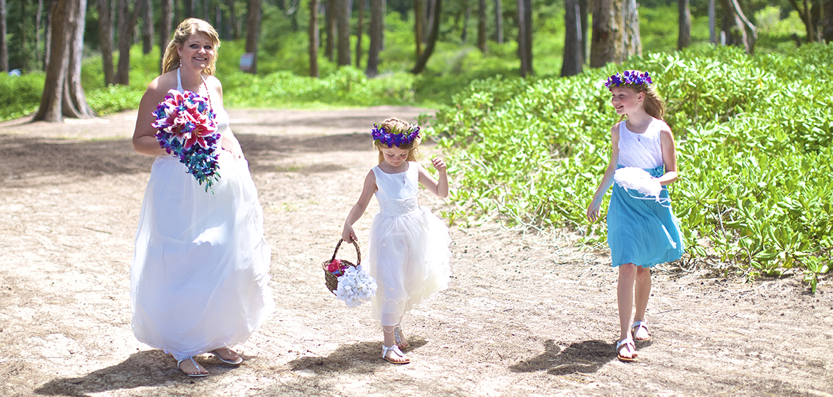 flower girls walking with the bride with purple head leis