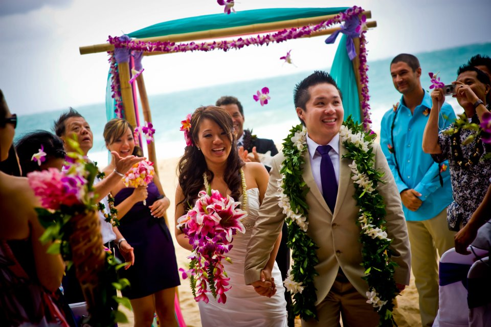 orchid purple flowers in the air as the newlyweds walk down the aisle sandy way