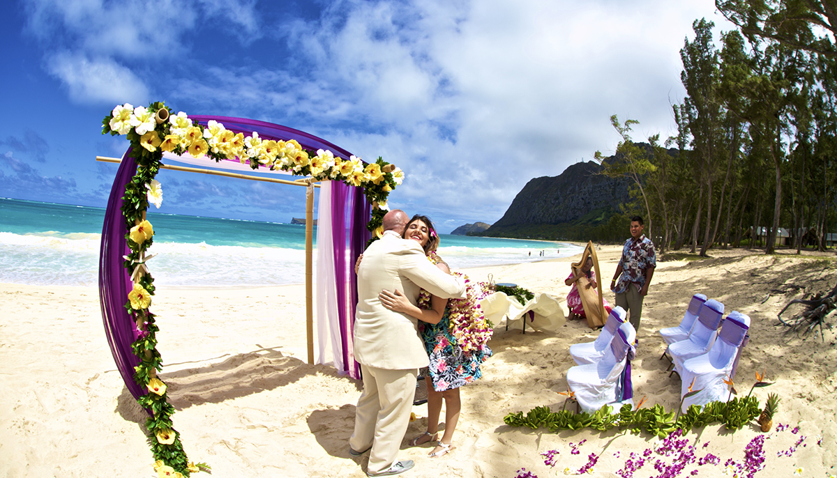 beach arch with yellow flowers as the groom gives a hug to his sister