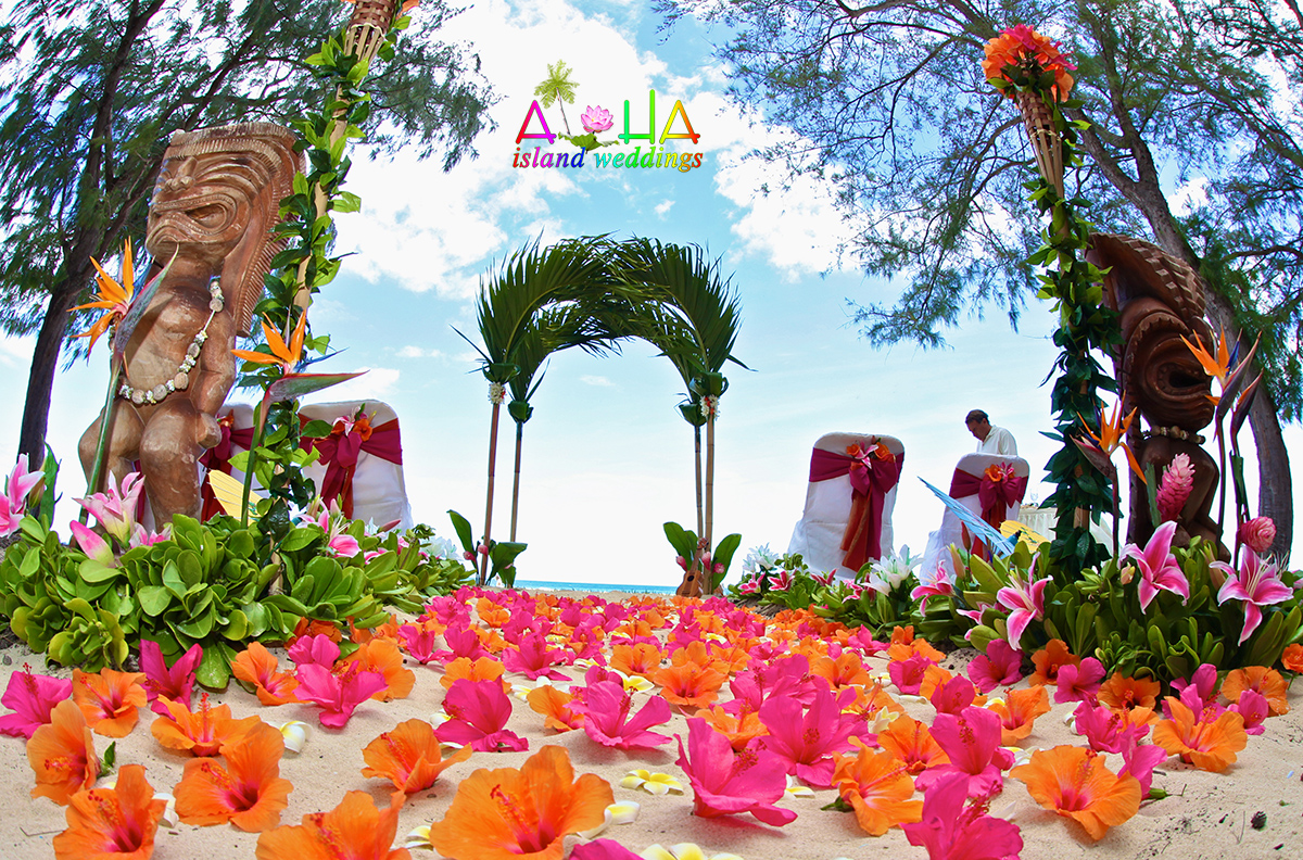 Hawaii beach wedding with tiki men pre wedding with orange and pink Hawaiian tropical flowers