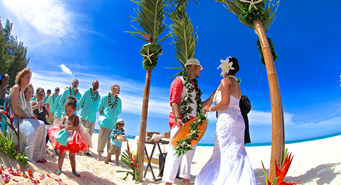 embracing the ceremonial symbol of the Hawaiian padal for the canoe at thier wedding