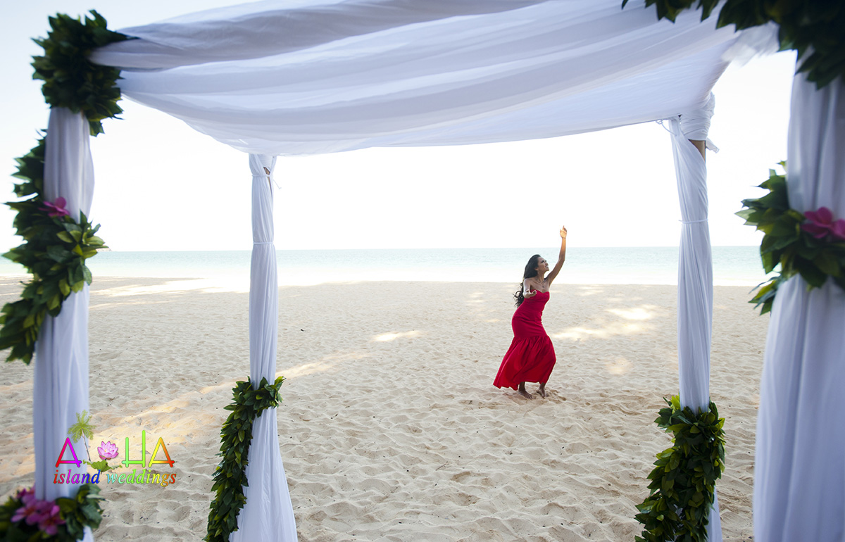 The Hula dancer sways her hips to the sound of the sea by the side of a bamboo white arch