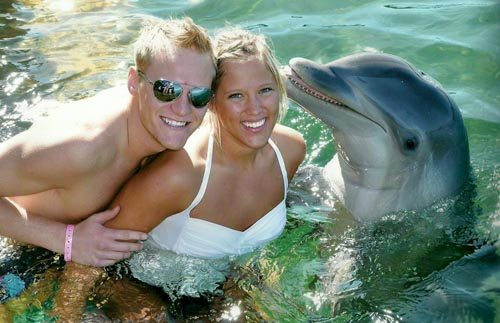 our wedding couple posing with a dolphin