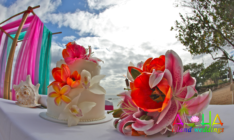 cake on the beach at paradise cove with pink and bright color flowers