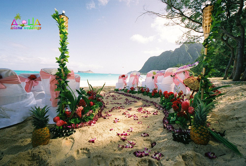 Purple orchids and pineapples with light pink sash chairs with the beach and mountains