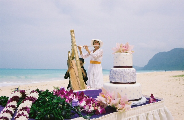 wedding cake on the beach in Hawaii with a harp and flute in the background