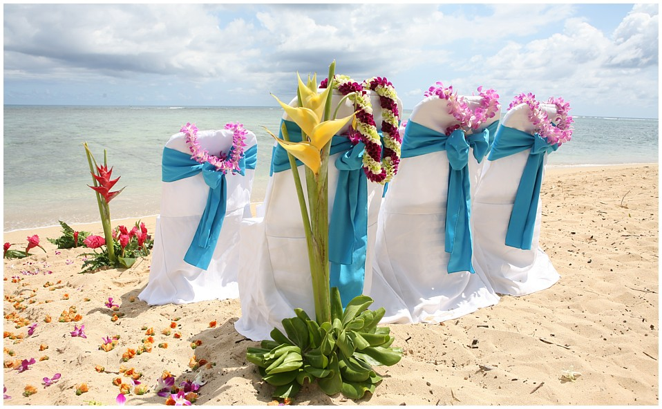 Chairs with flower leis over them on the beach in Hawaii