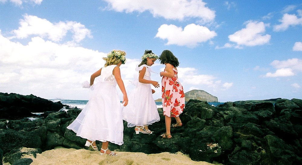 flower girls play on the lava rocks next to the weddign of Hawaii