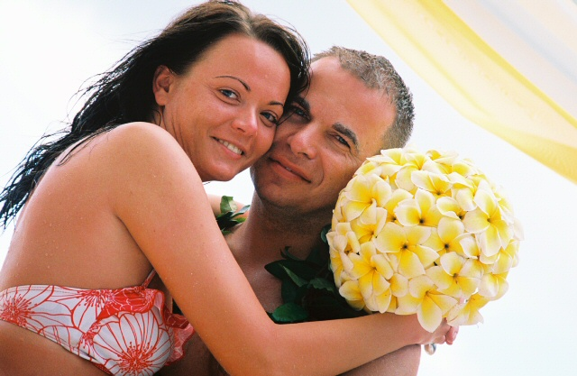 bride in bathing suite hold bouquet of yellow plumerias
