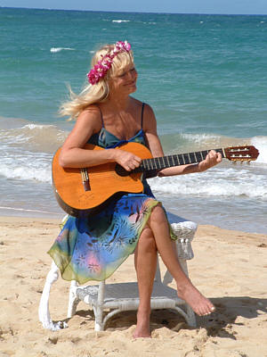 kim marie playing the guitar on th ebeach at a wedding
