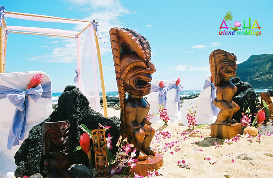 Tiki gods stand guard at this wedding setup with lava rocks and a arch