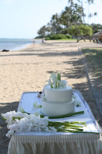 all white wedding cake on the table over looking diamond head beach