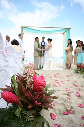 Getting married on the  beach with white wedding chairs and pink flowers