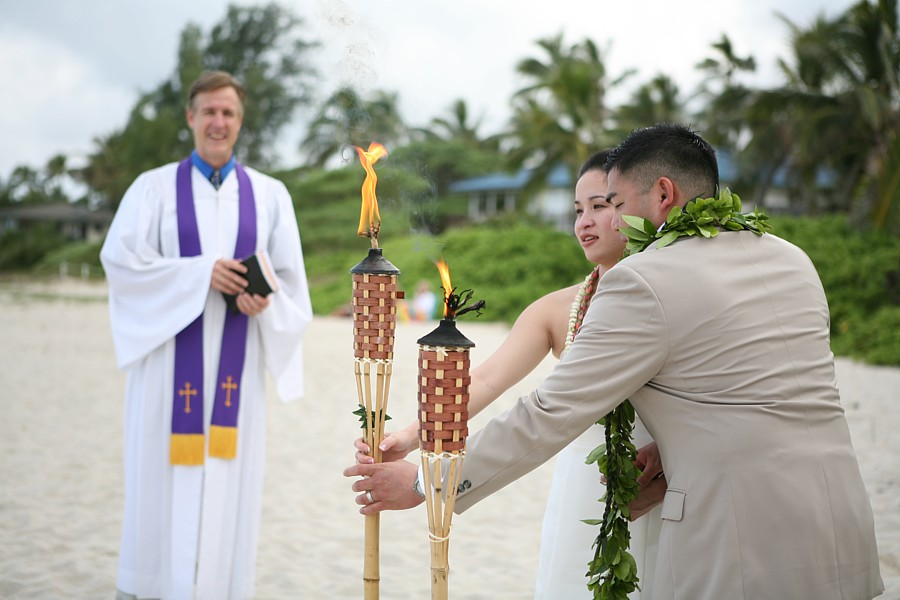 Chris cain over looks the couple lighting the fire torch at their wedding