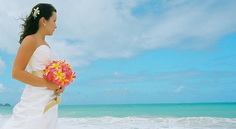 bride looking over the ocean with her pink and yellow bouquet